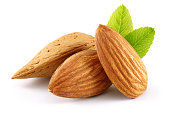 Almonds and green leaves isolated on white