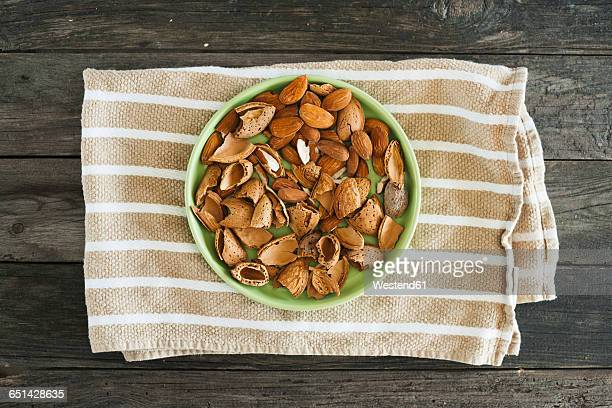 Almonds, green plate, kitchen towel on wood