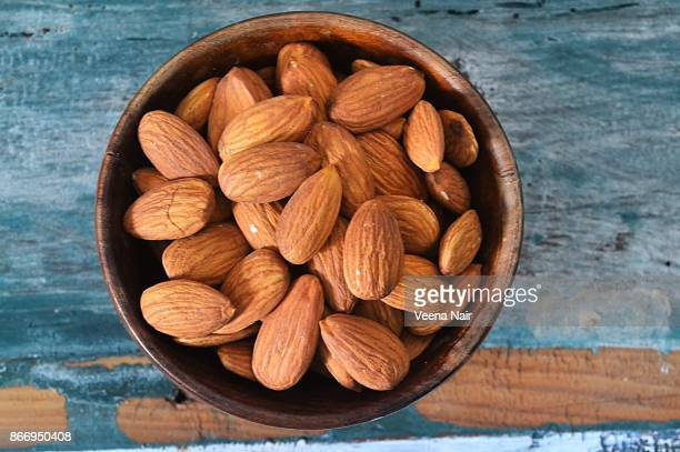 Almonds in a wooden bowl against textured background