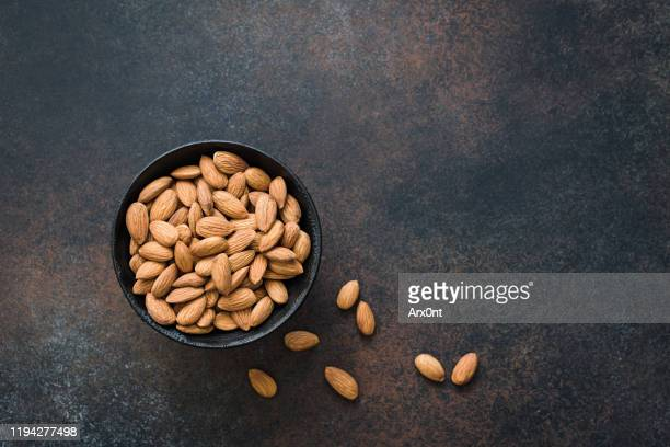 almonds in bowl on background - almond stock pictures, royalty-free photos & images