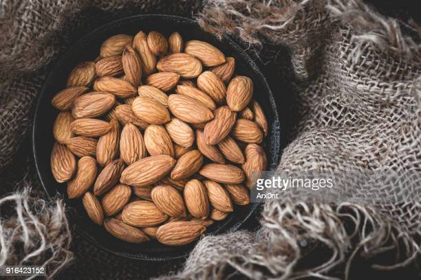 almonds in bowl on old burlap - organic compound stock photos and pictures