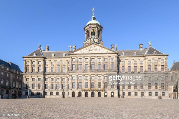 Almost deserted Dam square with the Royal Palace of Amsterdam in Amsterdam during a weekday morning following the advice of the Dutch government to...