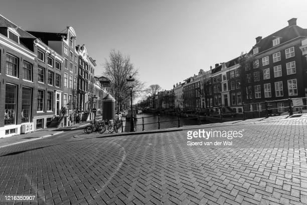 Almost deserted Herengracht canal and street in Amsterdam during a weekday morning following the advice of the Dutch government to stay at home for...