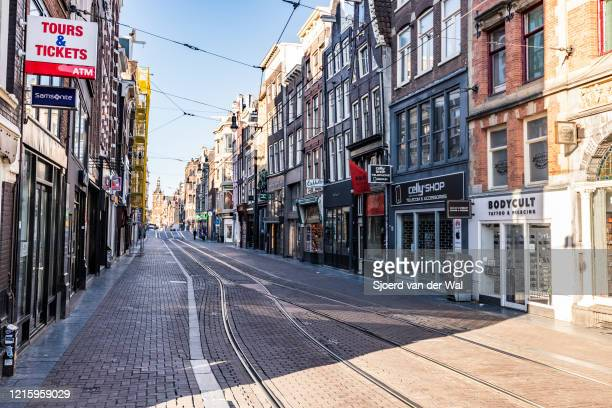 Almost deserted Leidsestraat shopping street in Amsterdam during a weekday morning following the advice of the Dutch government to stay at home for...