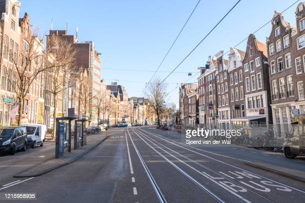 Almost deserted Nieuwezijds Voorburgwal street in Amsterdam during a weekday morning following the advice of the Dutch government to stay at home for...