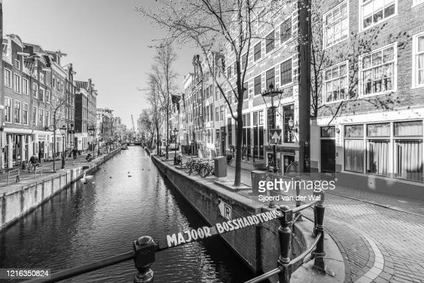Almost deserted red light district canal at the Oudezijds Achterburgwal in Amsterdam during a weekday morning following the advice of the Dutch...