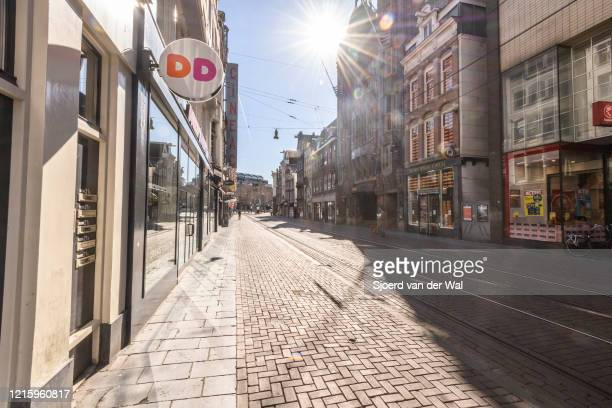 Almost deserted Reguliersbreestraat shopping street in Amsterdam during a weekday morning following the advice of the Dutch government to stay at...