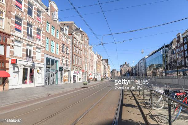Almost deserted Rokin street and canal in Amsterdam during a weekday morning following the advice of the Dutch government to stay at home for...