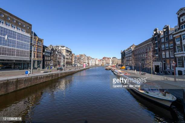 Almost deserted Rokin street and canal with tourboats in Amsterdam during a weekday morning following the advice of the Dutch government to stay at...
