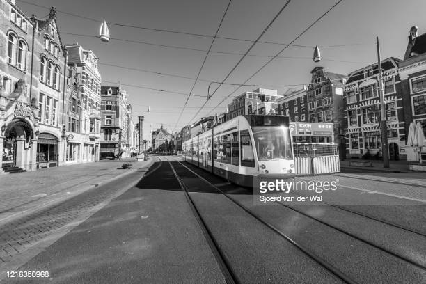 Almost deserted Rokin street with a passing tram in Amsterdam during a weekday morning following the advice of the Dutch government to stay at home...