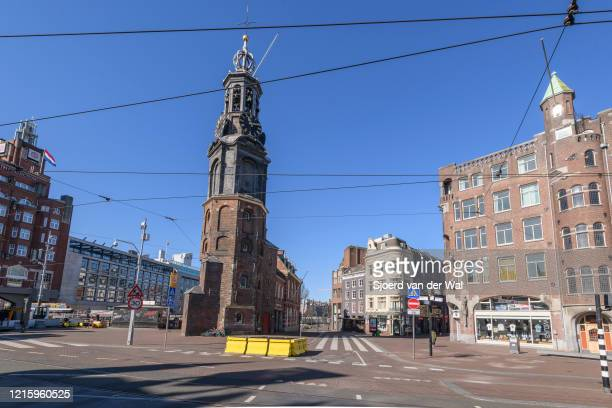 Almost deserted street at the Munt tower in Amsterdam during a weekday morning following the advice of the Dutch government to stay at home for...