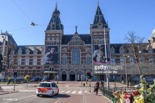 Almost deserted streets and square at the Rijksmuseum with a police car on patrol in Amsterdam during a weekday morning following the advice of the...