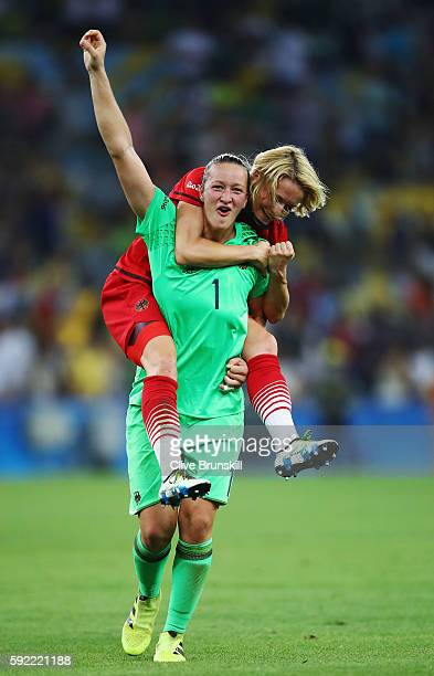 Almuth Schult of Germany and Saskia Bartusiak of Germany celebrate victory in the Women's Olympic Gold Medal match between Sweden and Germany at...