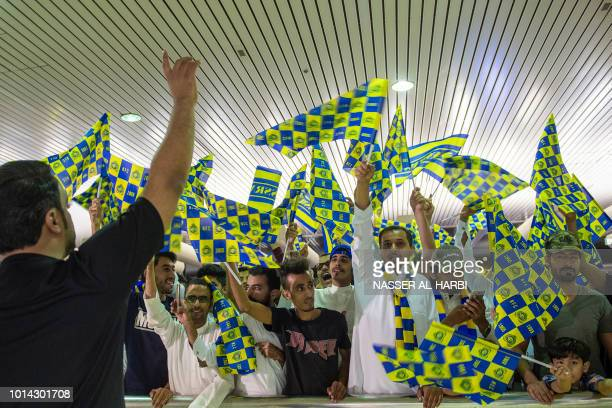 AlNassr supporters wave the club flags as they gather to welcome Nigerian forward Ahmed Musa upon his arrival at King Khalid International Airport in...