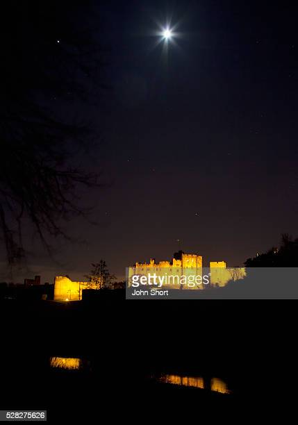 alnwick castle illuminated at night with the moon shining in the sky; alnwick northumberland england - alnwick castle stock photos and pictures