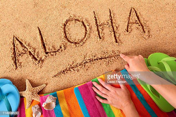 aloha beach message with towel and starfish - aloha stock pictures, royalty-free photos & images