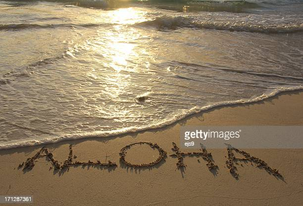 Aloha written on Hawaii Pacific ocean beach sand