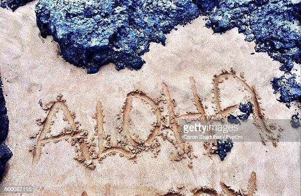 aloha written on sand at beach - aloha stock pictures, royalty-free photos & images