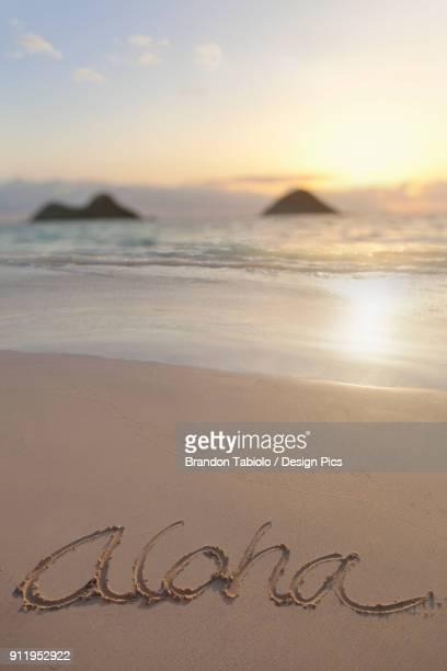 Aloha Written On The Sand On Lanikai Beach In Kailua With Mokulua Twin Islands In The Background At Sunrise