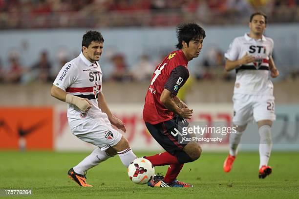 Aloisio of Sao Paulo and Kazuya Yamamura of Kashima Antlers compete for the ball during the pre season friendly match between Kashima Antlers and Sao...