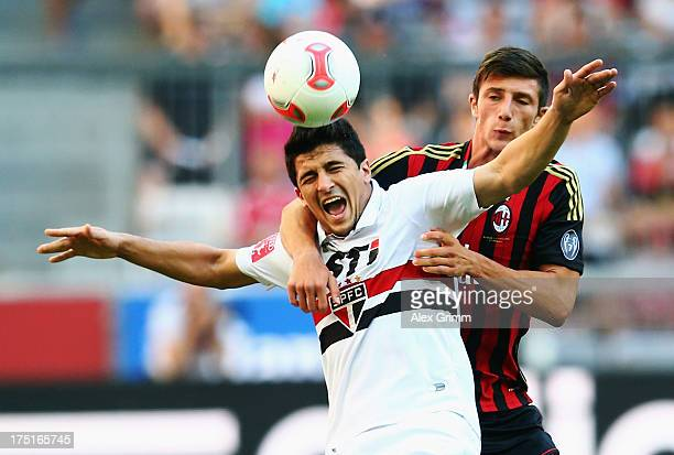 Aloisio of Sao Paulo is challenged by Davide Pacifico of Milan during the Audi Cup match between FC Sao Paulo and AC Milan at Allianz Arena on August...