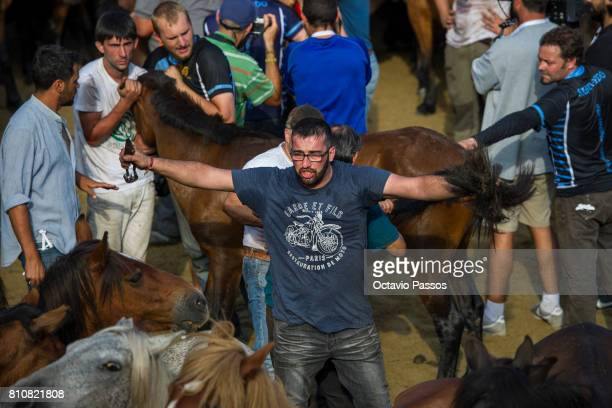 A 'Aloitadore' shows off the cut mane of a wild horse during the 'Rapa Das Bestas' a traditional event in the Spanish northwestern village of...