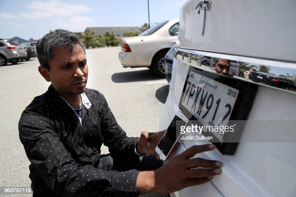 Alok Damireddy uses a smart phone app to make adjustments to a digital license plate made by Bay Area company Reviver Auto part of a pilot project...
