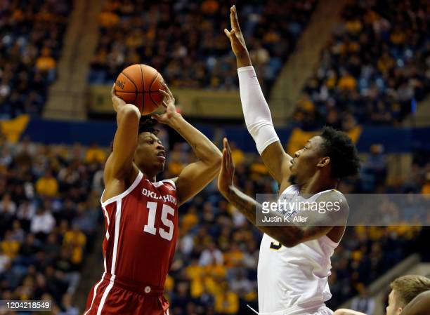 Alondes Williams of the Oklahoma Sooners pulls up for a shot against Gabe Osabuohien of the West Virginia Mountaineers at the WVU Coliseum on...