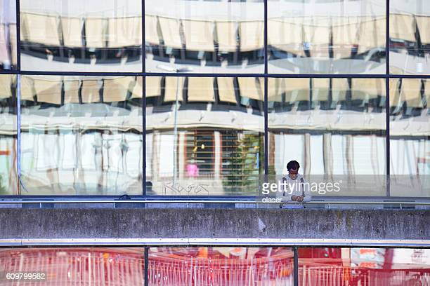 Alone black man, using phone, Sergels Torg, Stockholm
