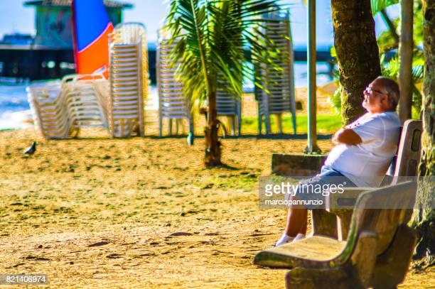 alone man sitting on bench observes the sea at perequê beach in ilhabela, brazil. - sentar se imagens e fotografias de stock