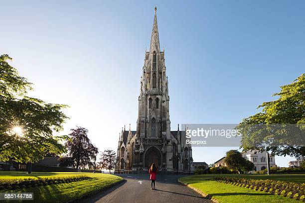 alone woman at the first church of otago in dunedin, new zealand. - dunedin new zealand stock pictures, royalty-free photos & images