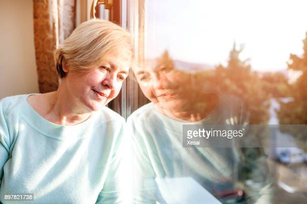 alone woman day dreaming by the window - one senior woman only stock pictures, royalty-free photos & images