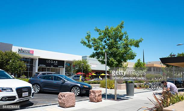 Along California Street on a sunny day in Palo Alto a Tesla automobile pulls into a parking space while a young man sits and uses his smartphone Palo...