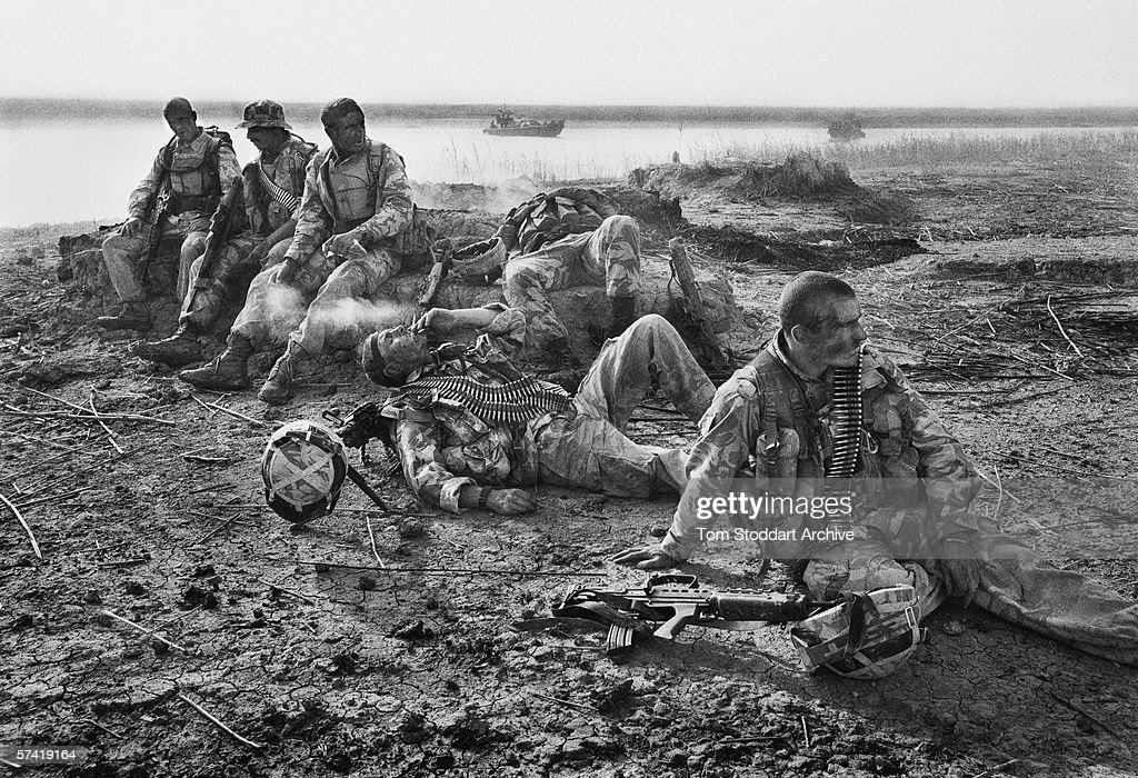 Along the Khawr Az Zubayr waterway in the marshes of southern Iraq, British Royal Marines from 539 Assault Squadron have been under fire during a night time patrol, and have just been told that one of their comrades has been killed. Tiredness and grief overcome them. 2003.