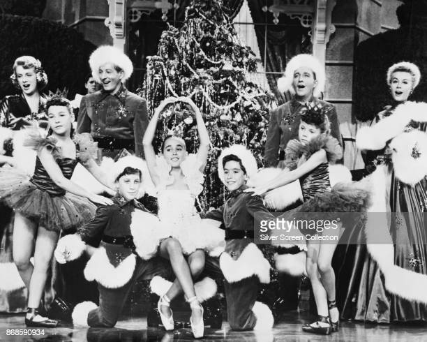 Along with a group of unidentified child actors actors Rosemary Clooney Danny Kaye Bing Crosby and VeraEllen sing in a scene from 'White Christmas'...