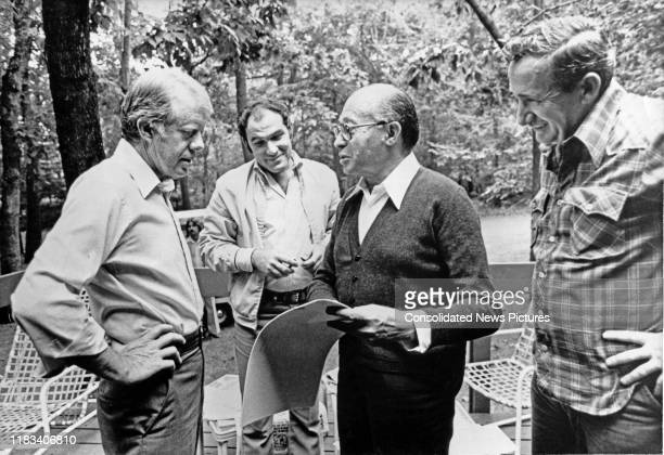 Along with a pair of unidentified aides, US President Jimmy Carter and Israeli Prime Minister Menachem Begin look at photographs during the...