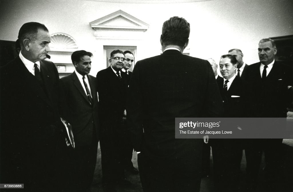 Along with his Vice President Lyndon Johnson (1908 - 1973) (left), US President John F Kennedy (1917 - 1963) (center, back to camera) meets with members of a congressional delegation in the Oval Office, Washington DC, 1961.