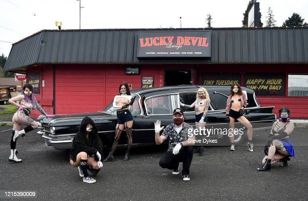 Along with owner Shon Boulden center exotic dancers pose for a photograph outside the Lucky Devil as they prepare to go out on a delivery on March 27...