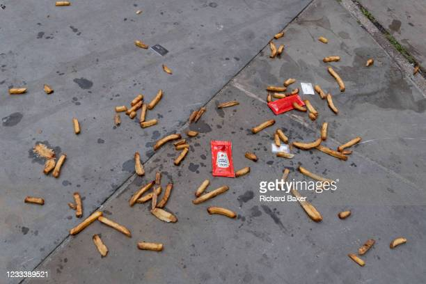 Along with sachets of salt and tomato ketchup, the remains of a portion of chips lie scattered on the pavement on London's Southbank, on 10th June...