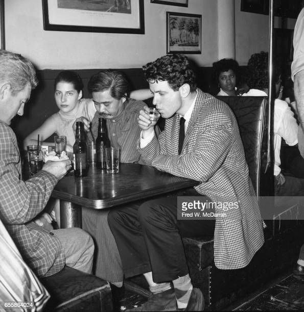 Along with unidentified others American artist Matsumi Kanemitsu and musician composer and conductor David Amram sit in a booth at the Cedar Street...