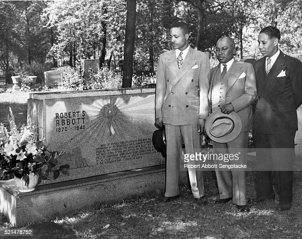 Along with unidentified others, American newspaper publisher John H Sengstacke , of the Chicago Defender, visits the gravesite of his uncle, Defender...