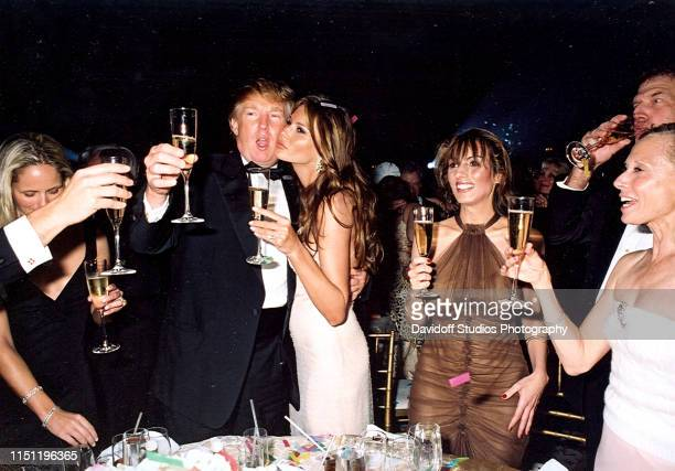 Along with unidentified others American real estate developer Donald Trump and his girlfriend model Melania Knauss raise their glasses for a New...