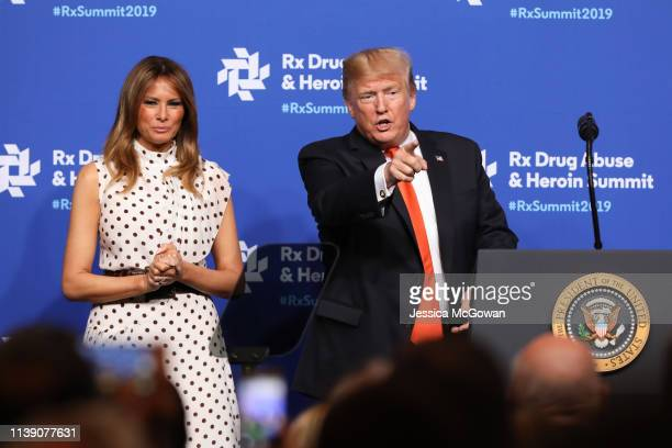 Alongside first lady Melania Trump President Donald Trump points at members of the audience after a speech at the Rx Drug Abuse Heroin Summit on...