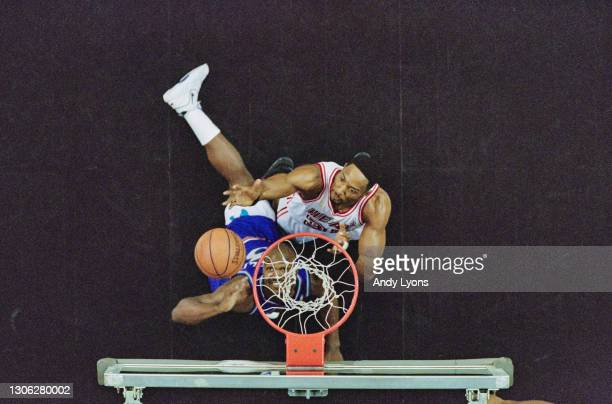 Alonzo Mourning, Center and Power Forward for the Miami Heat and Bryon Russell of the Utah Jazz challenge for the basketball beneath the hoop during...