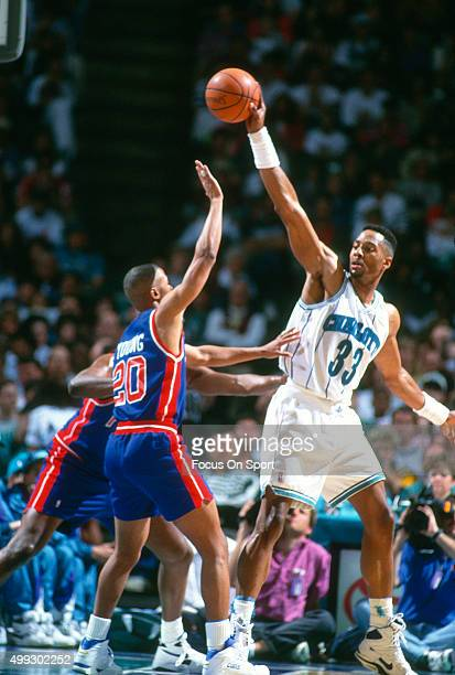Alonzo Mourning of the Charlotte Hornets looks to pass the ball over the top of Danny Young of the Detroit Pistons during an NBA basketball game...