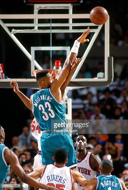 Alonzo Mourning of the Charlotte Hornets passes the ball against New York Knicks during an NBA basketball game circa 1992 at Madison Square Garden in...