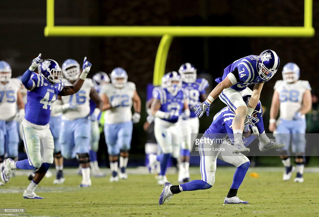 Alonzo Saxton II #21 intercepts the ball as teammate Ben Humphreys #34 of the Duke Blue Devils celebrates during their game against the North Carolina Tar Heels at Wallace Wade Stadium on November 10, 2016 in Durham, North Carolina. The Duke Blue Devils defeated the North Carolina Tar Heels 28-27.