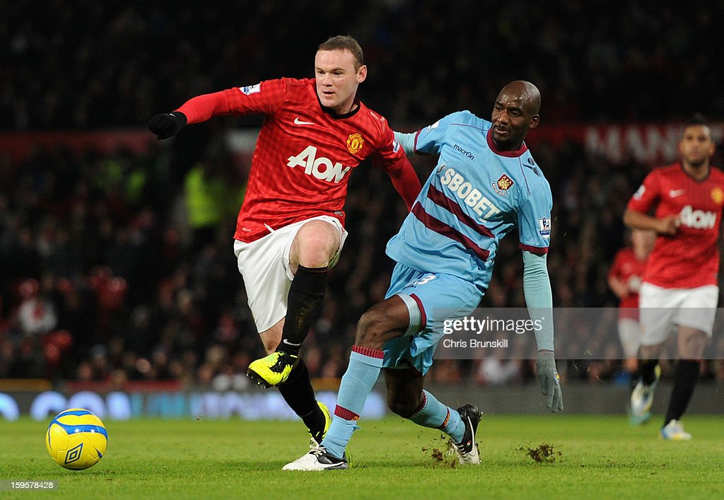Alou Diarra of West Ham United challenges Wayne Rooney of Manchester United during the FA Cup with Budweiser Third Round Replay match between Manchester United and West Ham United at Old Trafford on January 16, 2013 in Manchester, England.