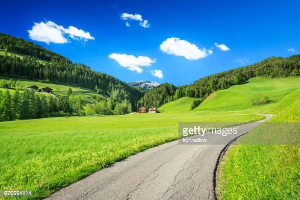 Alpen landskap - rullande kullar, ängar och landsväg