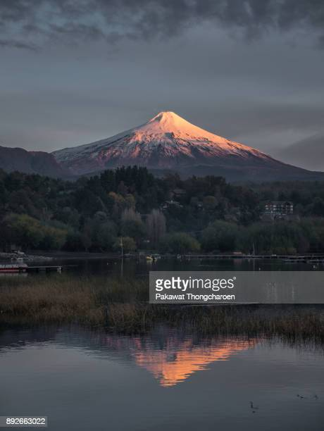 alpenglow villarrica volcano and reflection at sunset, chile - villarrica stock photos and pictures